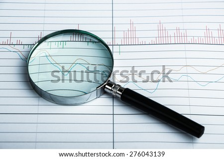 Magnifying glass is lying on the paper with financial graph.