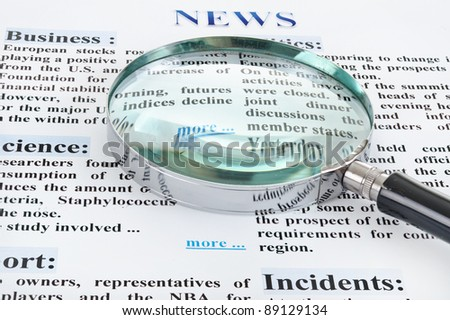 magnifying glass is on the news text - stock photo