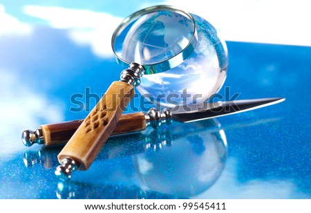 magnifying glass, knife and globe