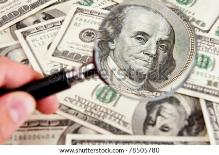 magnifying glass lies on  american dollars on white