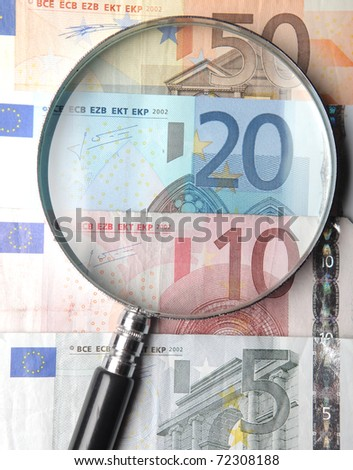 Magnifying glass lying on banknotes - stock photo