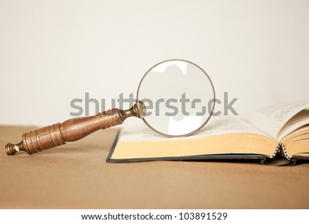 Magnifying glass on a book - stock photo