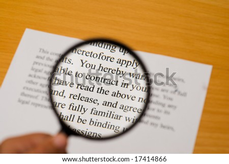 "Magnifying glass on a contract with selective focus on the word ""contract""."