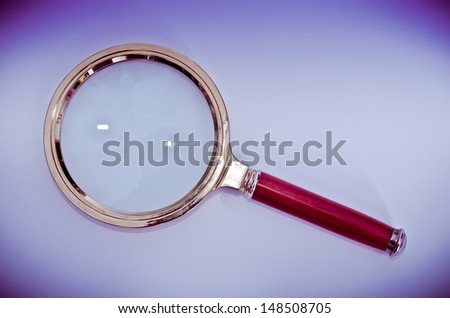 magnifying glass on a purple background - stock photo