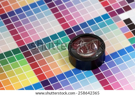 Magnifying glass on a very colorful test print - stock photo