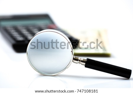 Magnifying Glass on blur calculator and money background