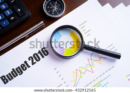 """Magnifying glass on colourful pie chart with """"Budget 2016"""" text on paper, dice, spectacles, pen, laptop calculator on wooden table - business, banking, finance and investment concept - stock photo"""