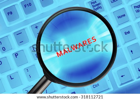 "Magnifying glass on computer keyboard with ""Malwares"" word."