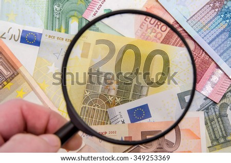 magnifying glass on different euro bills - stock photo