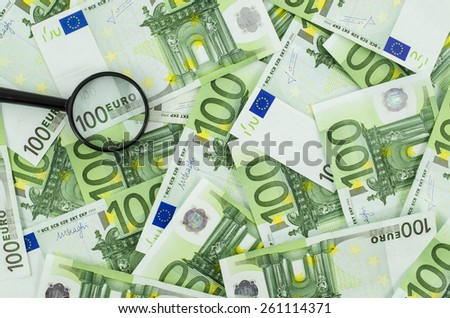 Magnifying glass on euro banknotes background - stock photo
