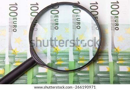 Magnifying glass on few hundred euro banknotes. - stock photo