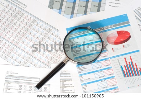 magnifying glass on financial documents