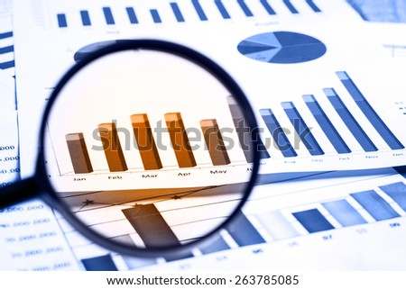 magnifying glass on financial report documents  - stock photo