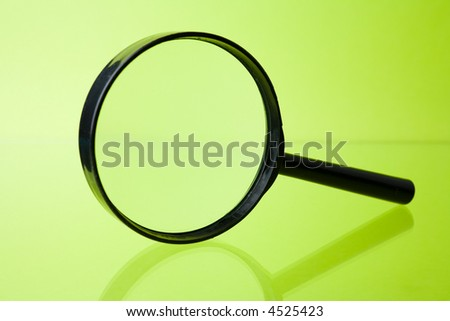 Magnifying glass on green background - stock photo