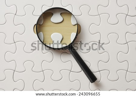 Magnifying Glass On Missing Puzzle - stock photo