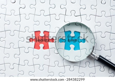 "Magnifying Glass On Missing Puzzle with ""Liability/Assets"" Word, Antonym Concept and Selective Focus - stock photo"
