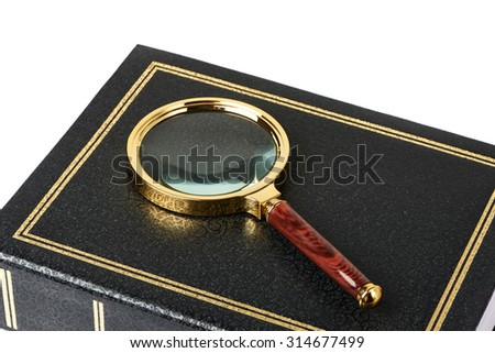 Magnifying glass on notebooks isolated on white background - stock photo
