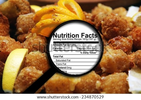 Magnifying glass on nutrition facts - stock photo