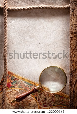 Magnifying glass on old parchment. - stock photo