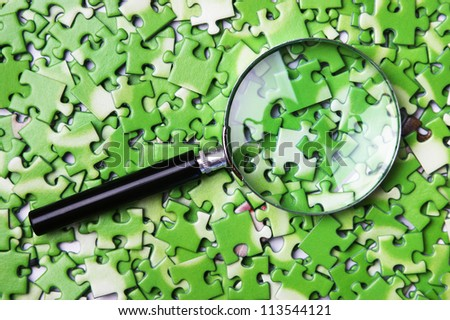 magnifying glass on pile of green puzzle