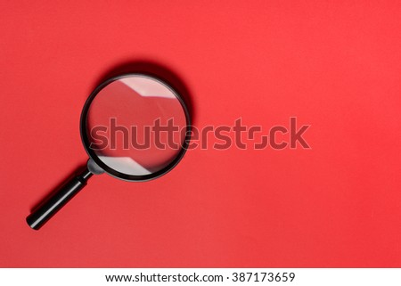 Magnifying glass on red background - stock photo