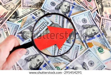 Magnifying Glass on the American Dollars Background with Arrow Up - stock photo