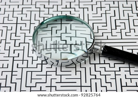 magnifying glass on the background of the labyrinth - stock photo