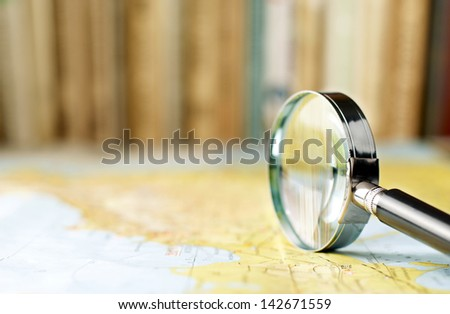 magnifying glass on the map and book in the background in the area of confusion - stock photo