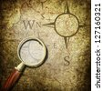 Magnifying glass on the old map - stock photo