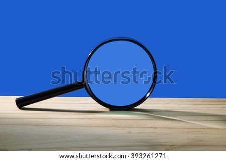 Magnifying Glass on Wooden Background - stock photo
