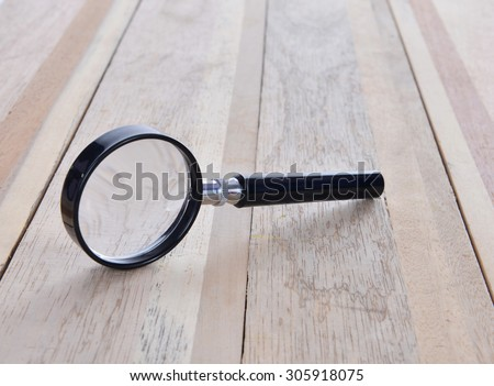 magnifying glass on wooden table - stock photo