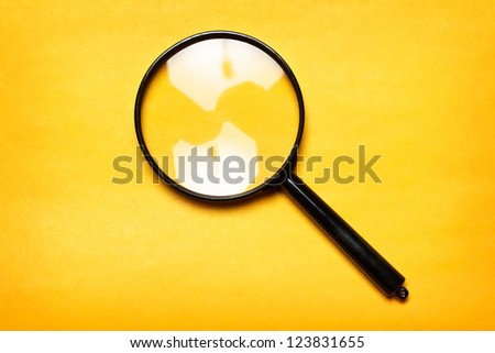 magnifying glass on yellow background - stock photo