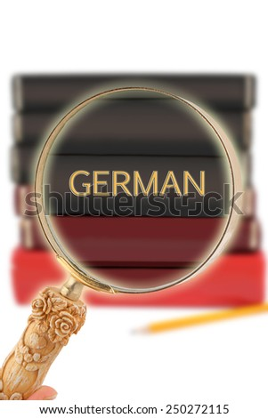 Magnifying glass or loop looking on an educational subject  - German - stock photo