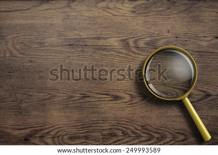 magnifying glass or loupe on wooden table - stock photo