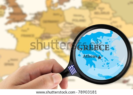 Magnifying glass over a map of Greece - stock photo