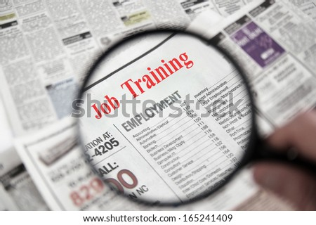 Magnifying glass over a newspaper classified section with Job Training text