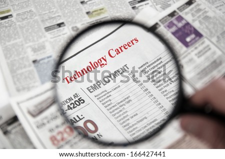 Magnifying glass over a newspaper classified section with Technology Careers text