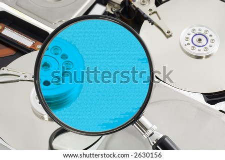 Magnifying glass over a opened hard drive depicting computer forensic - stock photo