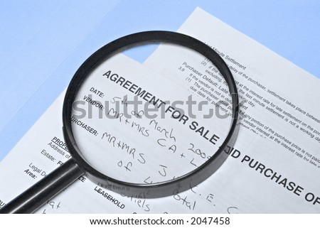 "Magnifying glass over ""agreement for sale"" on real estate contract."