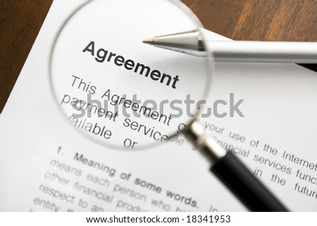 Magnifying glass over agreement paperwork and pen