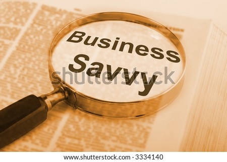 Magnifying glass over book, with words Business Savvy emphasised.