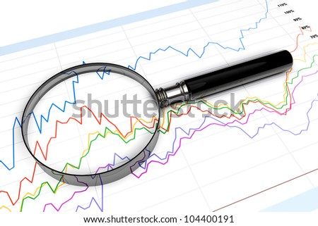 Magnifying glass over business diagram extreme closeup - stock photo