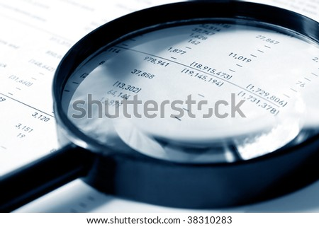 Magnifying glass over financial figures.  Shallow DOF, cyan tone. - stock photo