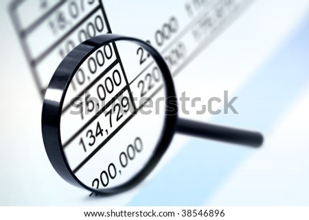 Magnifying glass over financial figures.  Very soft focus. - stock photo