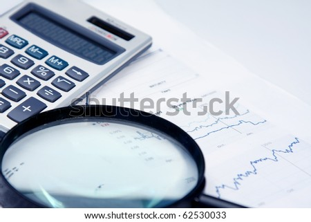 magnifying glass over financial paper