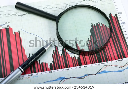 magnifying glass over graph - stock photo