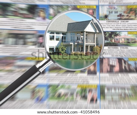 Magnifying glass over real estate section in newspaper - stock photo