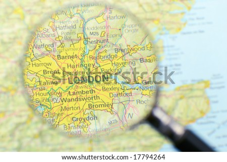 Magnifying glass over the map, focusing on London. - stock photo