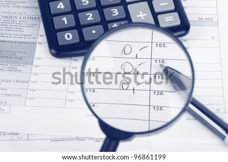 Magnifying glass over the tax form - stock photo