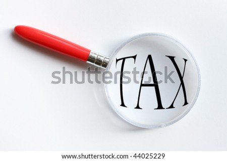 Magnifying Glass over the word tax - stock photo